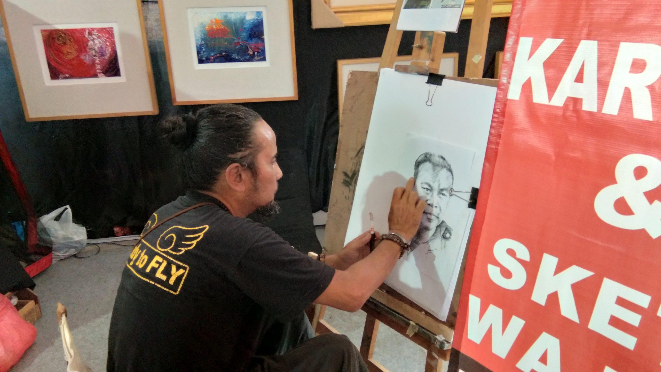 Foto : Salah satu pelukis di swarna warni sedang membuat sketsa wajah.