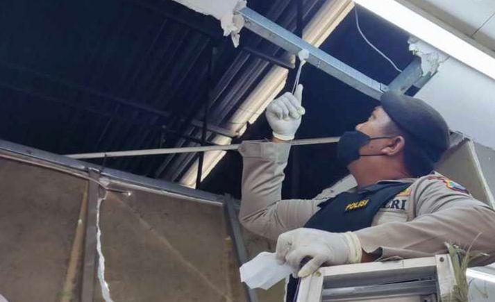Polisi saat menunjukan atap plafon yang dijebol pelaku pencurian di minimarket, Gedeg.